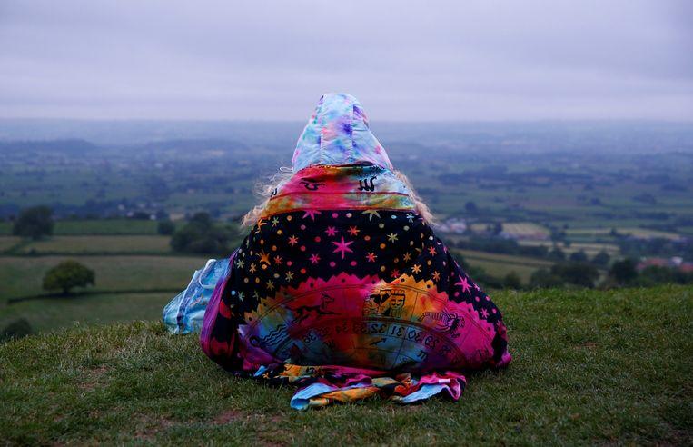 Turen in de verte, wachtend op de zonnewende. Deze persoon deed dat gisteren vanaf de Glastonbury Tor, een heuvel bij het Britse stadje Glastonbury. Tijdens de zonnewende bereikt de zon op het noordelijk halfrond haar hoogste punt. Het was ook de langste dag van het jaar. Beeld REUTERS