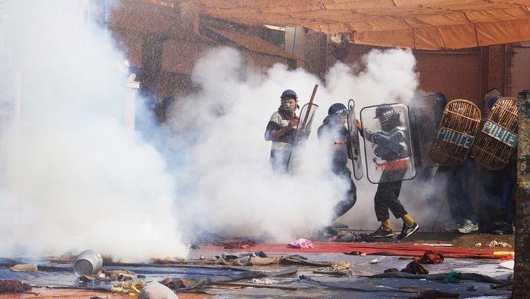 Agenten gaan de aanhangers van de goeroe met traangas te lijf. Beeld AP