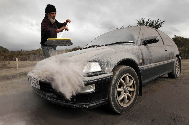 Vic Cassin sweeps ash from a car in Rangipo near Mount Tongariro, New Zealand after an eruption, Tuesday, Aug. 7, 2012. The volcano in New Zealand's central North Island has erupted for the first time in more than a century, sending out an ash cloud that is causing road closures and the cancellation of some domestic flights. (AP Photo/New Zealand Herald, Alan Gibson) AUSTRALIA OUT, NEW ZEALAND OUT Beeld AP