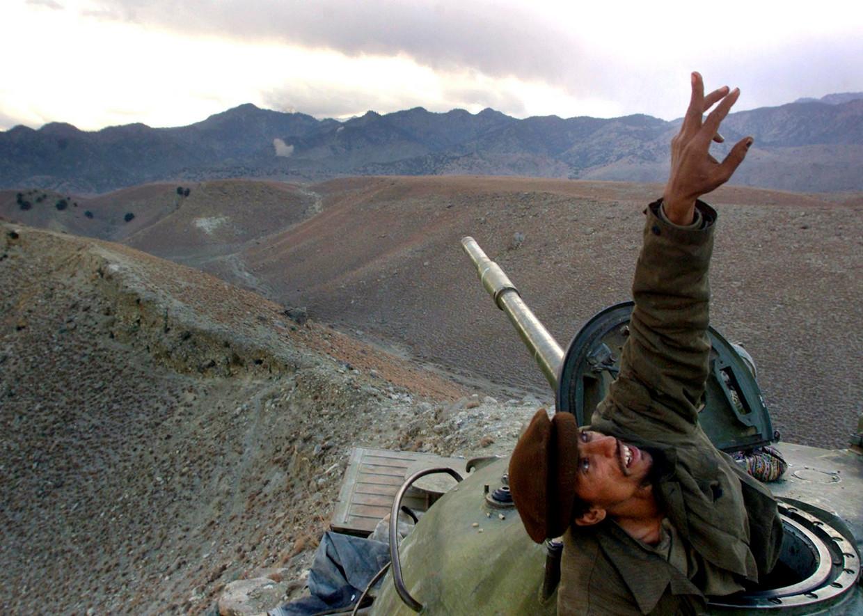 Een anti-Talibanstrijder wijst vanuit zijn tank op een Amerikaanse bommenwerper, die de Taliban vanuit de lucht komt bestoken in het gebied Tora Bora, december 2001. De steun aan anti-Talibanmilities zou in de jaren daarop enorme gevolgen hebben.  Beeld AP