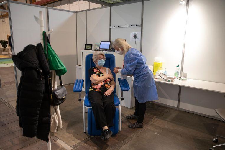 In Brussel wordt een vrouw ingeënt met het AstraZeneca-vaccin. In tegenstelling tot veel andere landen is België de afgelopen week gewoon doorgegaan met het toedienen van dit vaccin. Beeld BELGA
