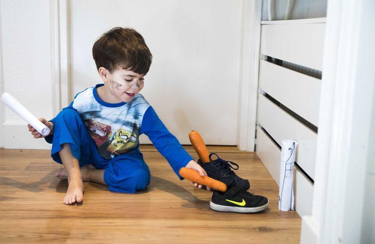 Een kind zet zijn schoentje. In de schoen zit een tekening of verlanglijstje voor de Sint en een wortel voor het paard van Sinterklaas.