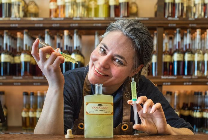 Fleur Kruyt van Van Kleef jenevers en likeuren bij haar nieuwste drankje 'Het Vaccin' toe te dienen met een injectiespuit.