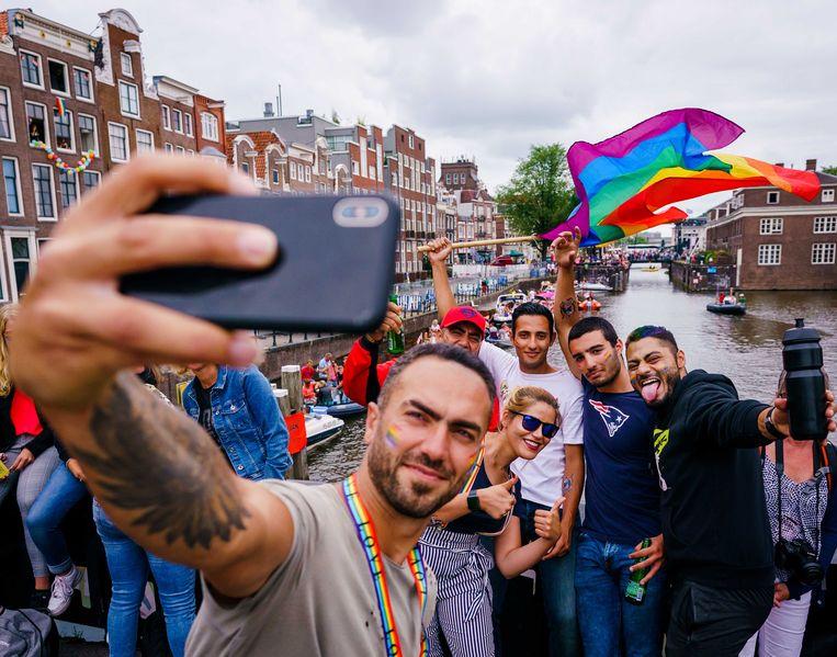 Feestvierende toeschouwers voorafgaand aan de botenparade in de grachten in 2019. Beeld ANP