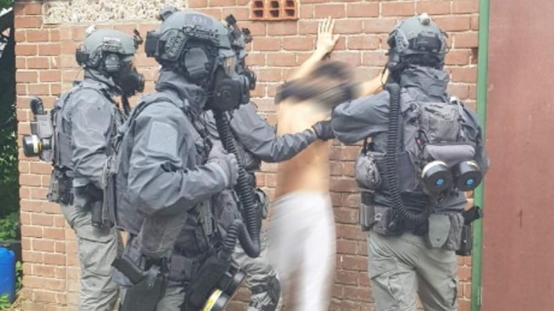 Eén van de verdachten wordt aangehouden na de inval in het drugslab in Drempt.