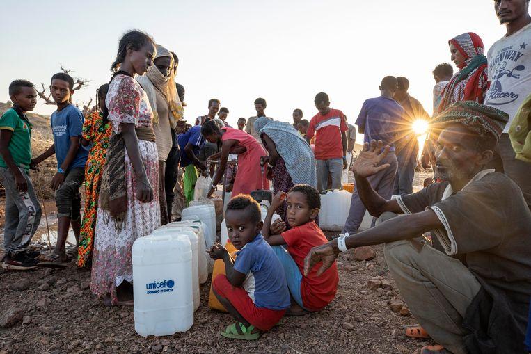 Gevluchte Tigrayers wachten over de grens in Soedan op hun beurt om water te halen.  Beeld AP