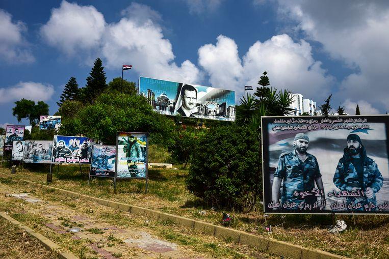 In de havenstad Latakia staan de afbeeldingen van jonge mannen die hun leven hebben gegeven voor Assad – 'de martelaren'. Beeld NYT MERIDITH KOHUT