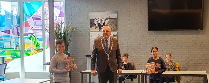Burgemeester Melis van de Groep deelt de eerste boekjes over de oorlog en bevrijding uit.