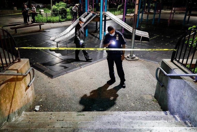 Twee politieagenten zoeken naar bewijs op een speelplaats waar twee personen gewond raakten bij een beschieting in Brooklyn, New York. Beeld AP