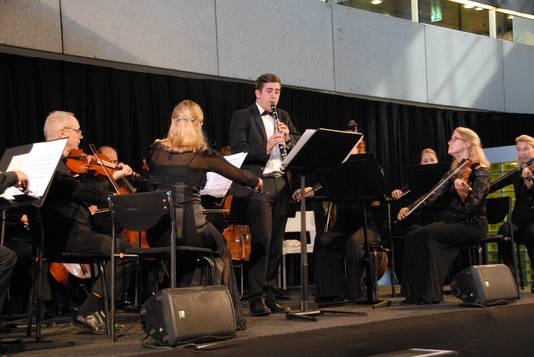 De jonge klarinettist Tim Huijbregts temidden van strijkers van Philharmonie Zuidnederland.
