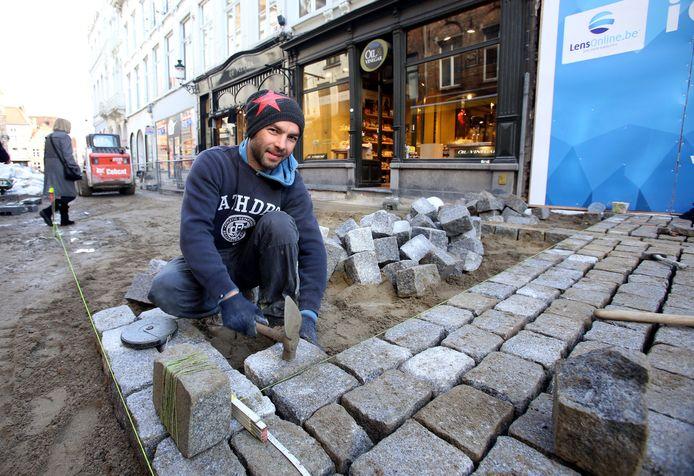 Een werkman legt een nieuw rijtje kasseien in de Geldmuntstraat tijdens de werken in 2015