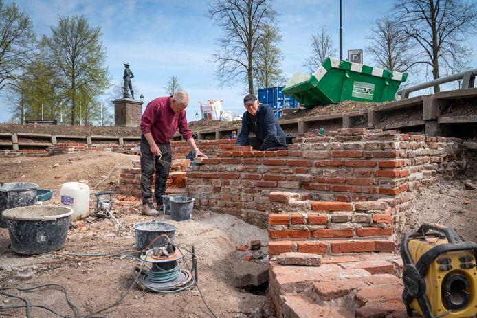 Cor Neijenhuis (rechts) vervangt samen met Sjaak Nas kapotte door nieuwe kloostermoppen. De onderste rij stenen is nog volledig origineel. Foto: Erik van 't Hullenaar.