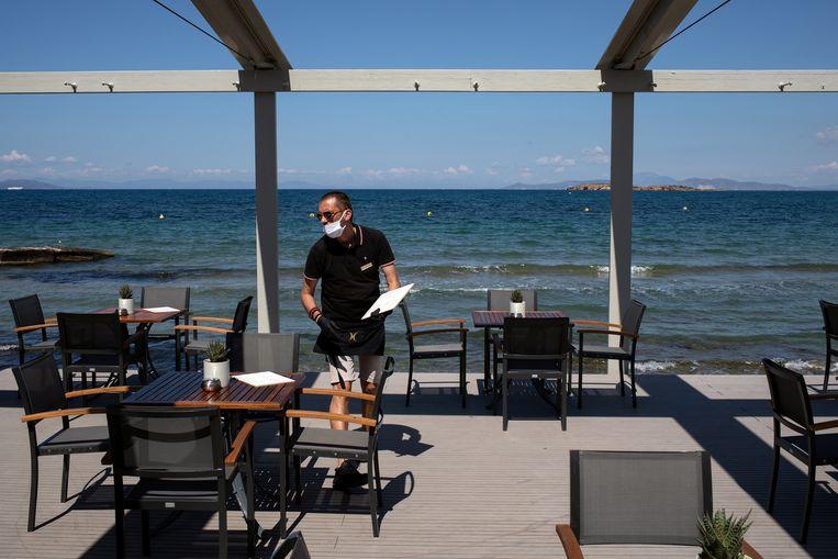 Een medewerker van de strandbar van het Divani Apollon Palace hotel legt menukaarten op de tafels. Beeld REUTERS