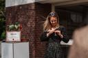 Judith van Willigen spelt haar lintje op. Op de achtergrond staan de oorkonde en het groenteboeket dat ze van De Vegetarische Slager ontving.