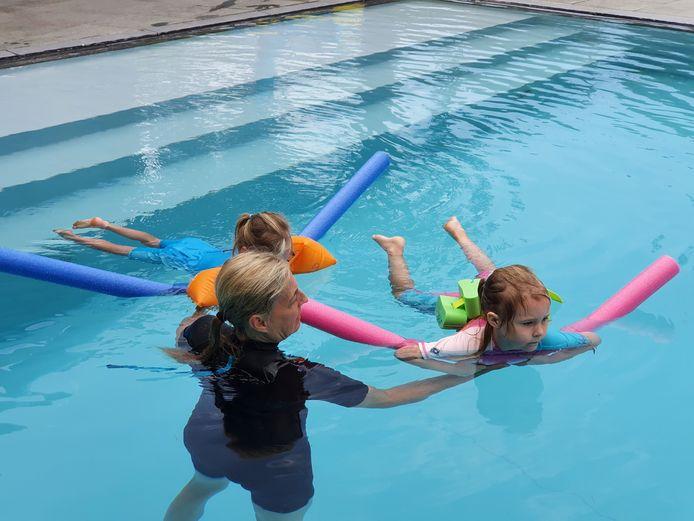Cindy Van Paesschen leert enkele kinderen de eerste kneepjes van het zwemmen.