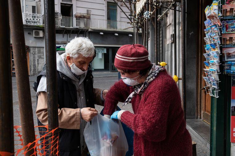 De eigenaresse van een tabakwinkel deelt eten uit aan families in Napels. Beeld Giulio Piscitelli