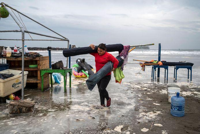 Een vrouw ruimt nog snel paraplu's, tafels en andere spullen op van het strand in Boca del Rio.