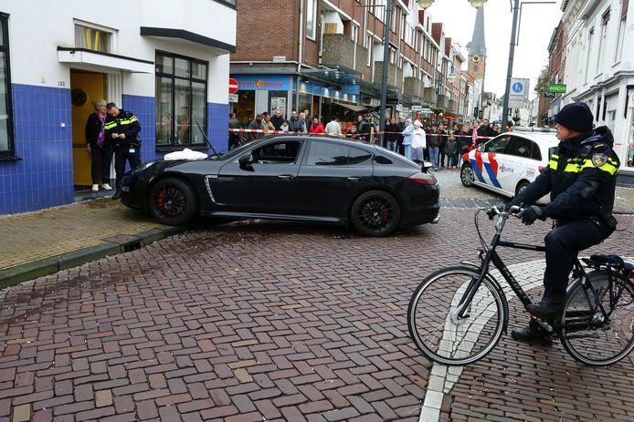 Een politieman bekijkt de Porsche, die voor de deur van het Blue Bandhuis de stoep opreed.