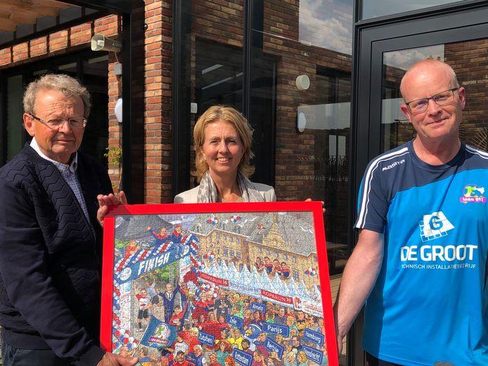 Bestuursvoorzitter Auke de Boer van Stichting Roparun en directeur Rachel Maréchal van het Familiehuis Daniel den Hoed krijgen uit handen van Hardinxvelder Jaap de Jager het eerste exemplaar van de cartoonpuzzel.