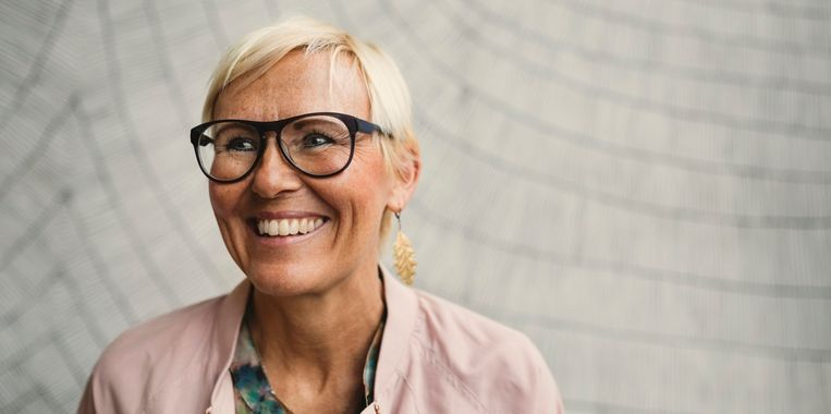 happy-businesswoman-wearing-eyeglasses-against-wall.jpg