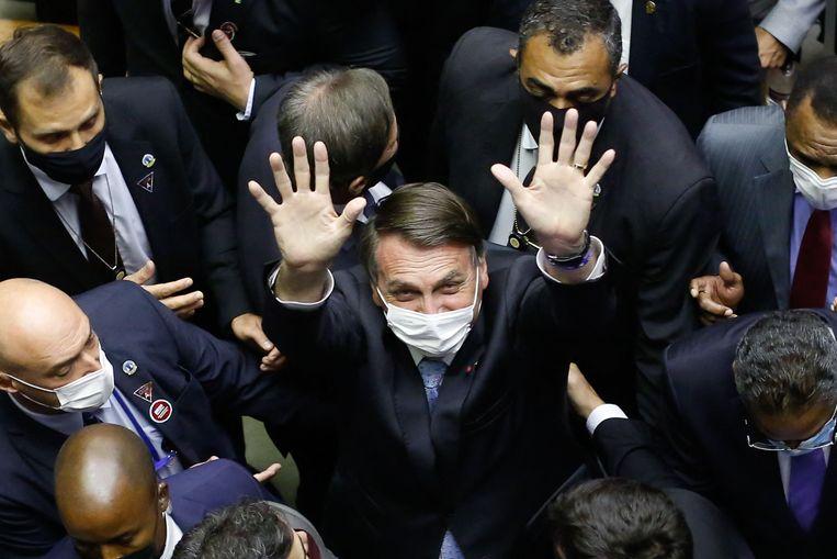 Braziliaans president Jair Bolsonaro zwaait naar de camera bij het verlaten van het Nationaal Congres.  Beeld AFP
