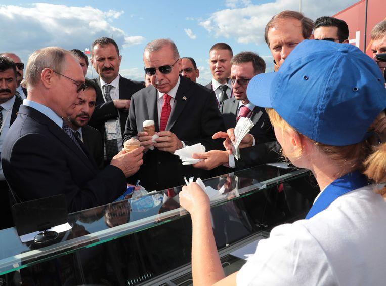 De Russische president Vladimir Poetin en zijn Turkse evenknie Recep Tayyip Erdogan in augustus 2019 bij de opening van een vliegshow even buiten Moskou. De leiders genieten van een ijsje op een hete zomerdag. Beeld AFP