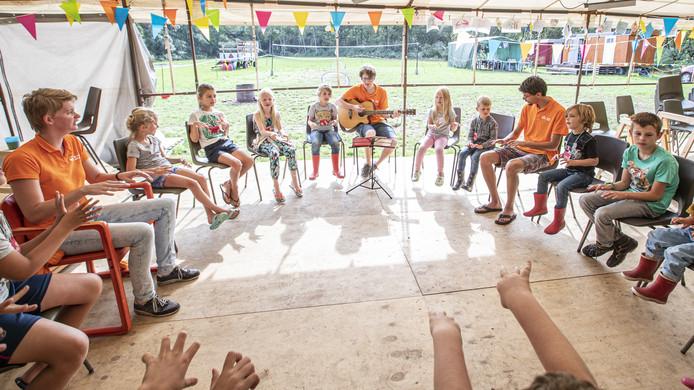 De Kinderclub begint elke ochtend met een aantal liedjes, Samuël begeleidt de kinderen op gitaar.