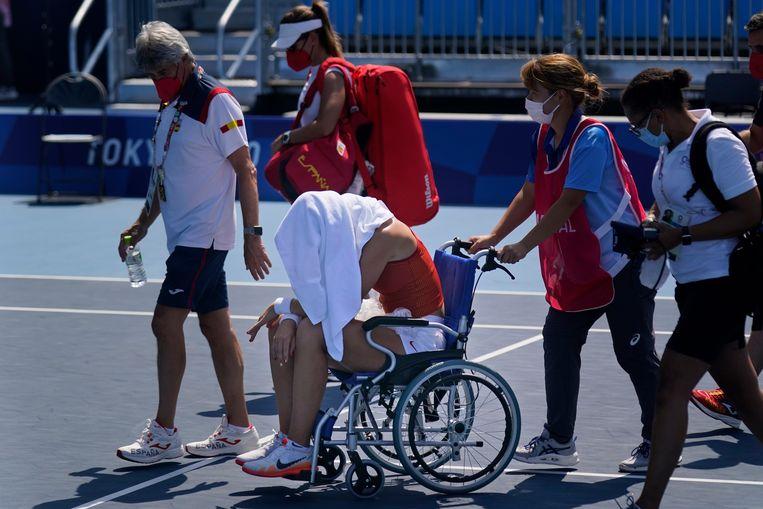 Paula Badosa wordt per rolstoel van de baan geholpen. Beeld AP