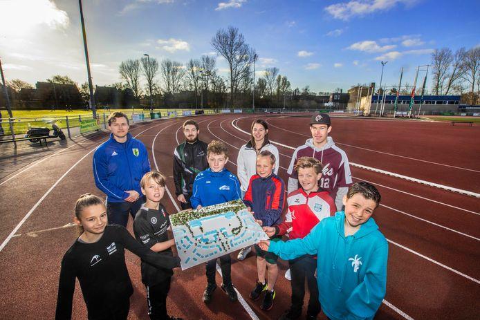 Kinderen en jongeren van verschillende Haagse sportclubs, in hun eigen tenue, tonen de maquette van het nieuwe sportcomplex. Straks hopen ze daar allemaal samen te trainen.
