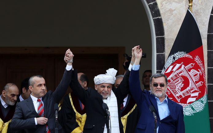 De Afghaanse president Ashraf Ghani (m) houdt de handen vast van vicepresidenten Amrullah Saleh (r) en Sarwar Danish (l) als teken van overwinning tijdens de eedaflegging, vandaag in het presidentiële paleis in Kaboel.