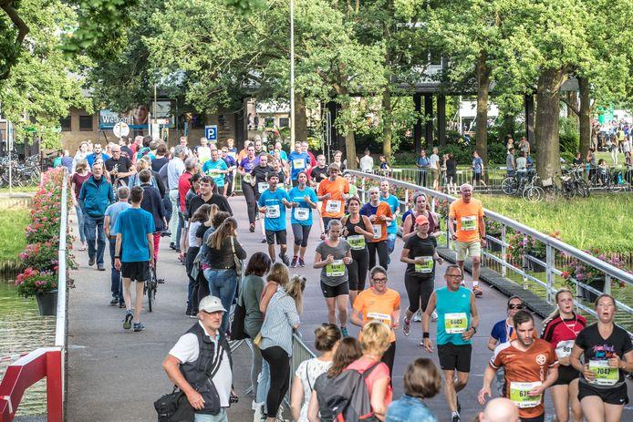 Lopers op het Kerkbrugje tijdens de Zwolse halve marathon, hoogtepunt van het atletiekjaar.