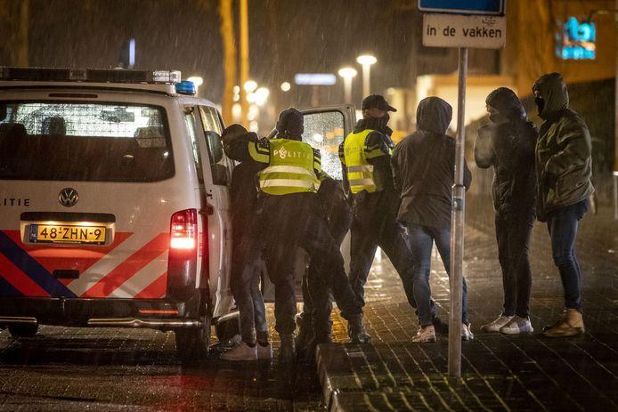 Arrestant die maandagavond vuurwerk gooide bij het winkelcentrum Groot Driene wordt gefouilleerd voordat hij richting politiebureau wordt afgevoerd