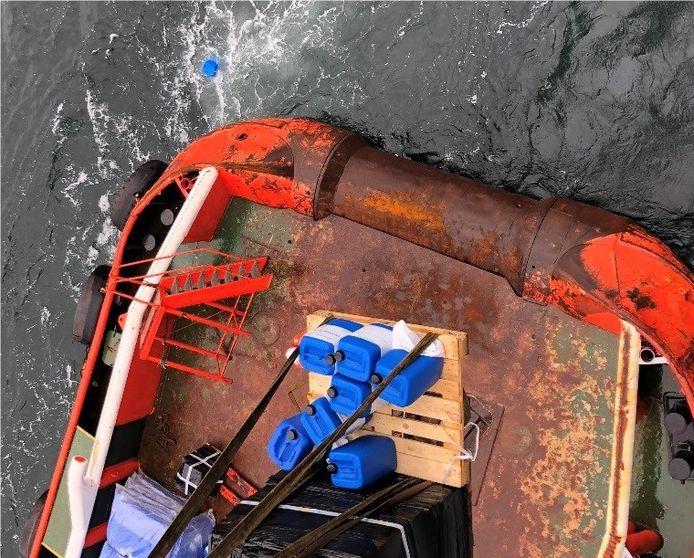 De blauwe jerrycans belandden vrijdag in zee en kunnen mogelijk aanspoelen.