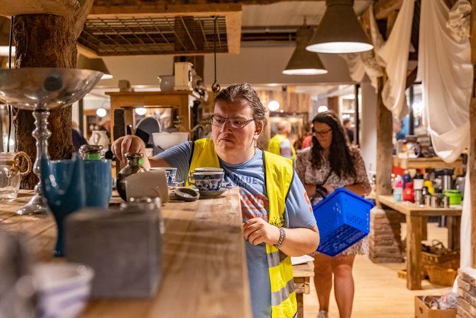 Medewerker Raymon Bult in de nieuwe kringloopwinkel in Hardenberg, met mensen van sociale werkvoorziening.