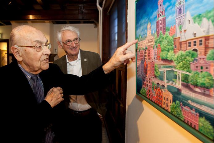 Kunstenaar Henry Verhagen en Gerard Kremers bekijken het schilderij 'Zicht op Amsterdam' in de expositie Lievelingen in Stadsmuseum Woerden.