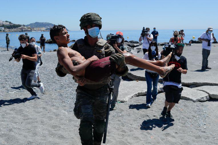 Enkele duizenden migranten zijn deze week vanuit Marokko naar de Spaanse stad Ceuta (een exclave aan de Afrikaanse kant van de Straat van Gibraltar) gezwommen, in de hoop op een beter leven in Europa. Een Spaanse militair draagt een van hen weg. Beeld REUTERS
