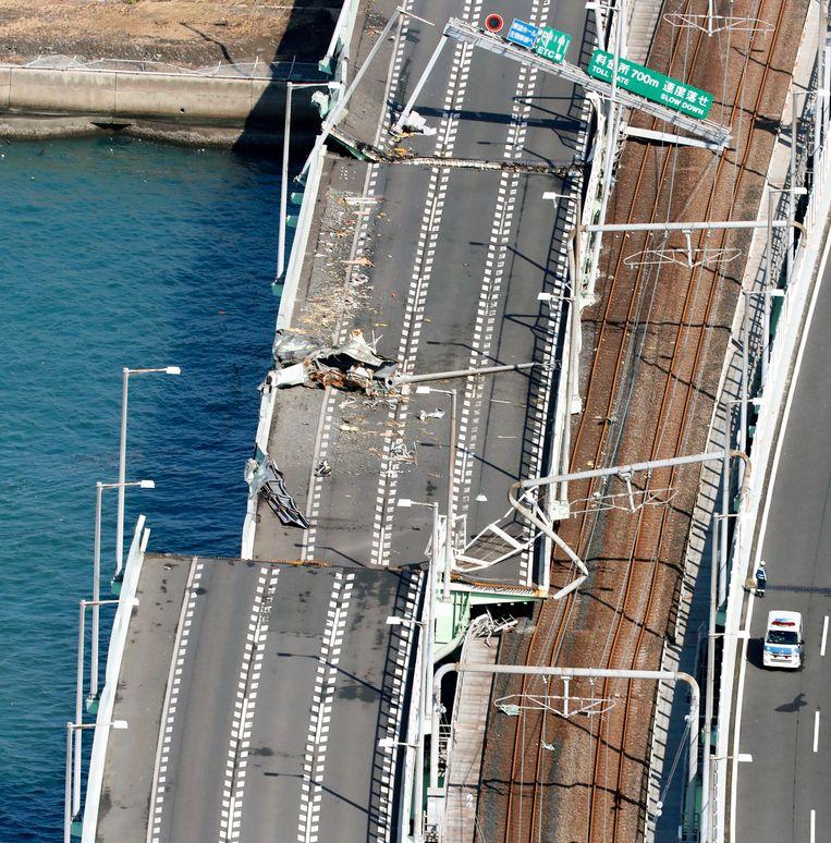 De weg die de luchthaven verbindt met het vasteland raakte zwaar beschadigd toen een zware tanker door de tyfoon tegen de brug gesmeten werd.