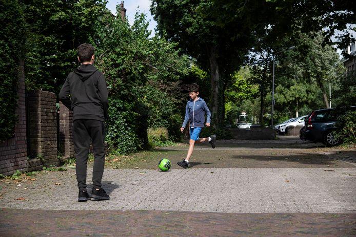 Loek (r) en Nadir voetballen in de Vermeerstraat in Nijmegen-Oost. De twee neefjes zijn bij oma op bezoek en voetballen noodgedwongen op straat omdat er in Oost nagenoeg geen veldjes zijn om te ballen.