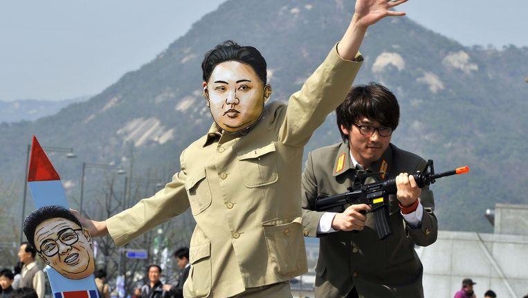 Een Zuid-Koreaanse activist draagt een masker van de Noord-Koreaanse leider Kim Jong Un om de spot te drijven met de mislukte raketlancering. Beeld AFP