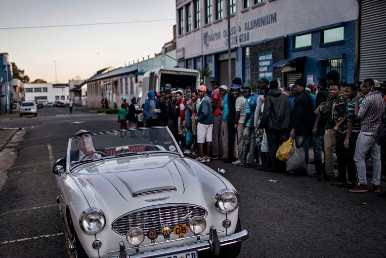 Kijken vanuit een luxe auto naar de rij bij de voedseluitgifte. Zuid-Afrika, afgelopen zomer.  Beeld AFP