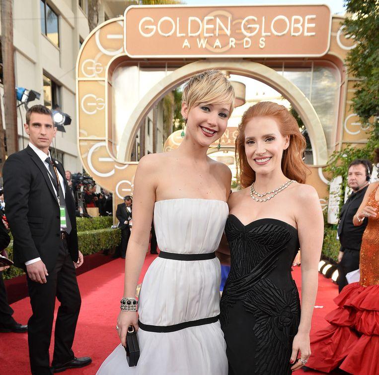 Actrices Jennifer Lawrence (links) en Jessica Chastain op de rode loper bij de Golden Globes. Beeld getty