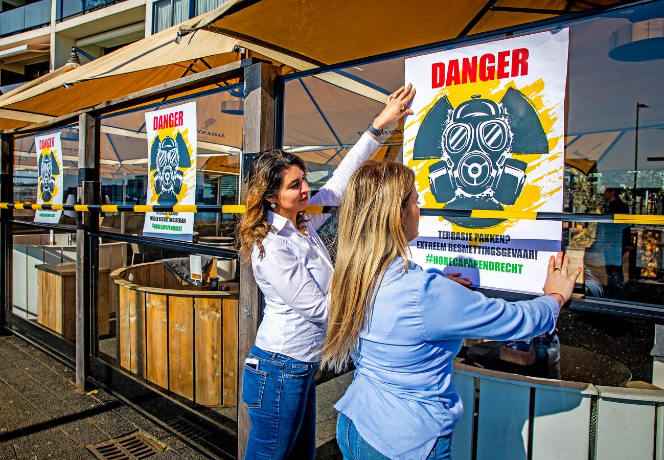 Medewerkers van restaurant Willaerts in Papendrecht hangen posters op tijdens de horeca-actie.