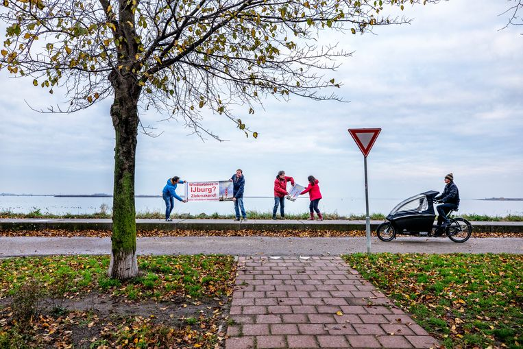 Actievoerders tegen windmolens op de plek waar windmolens moeten komen op het water op IJburg in Amsterdam. Beeld Raymond Rutting / de Volkskrant