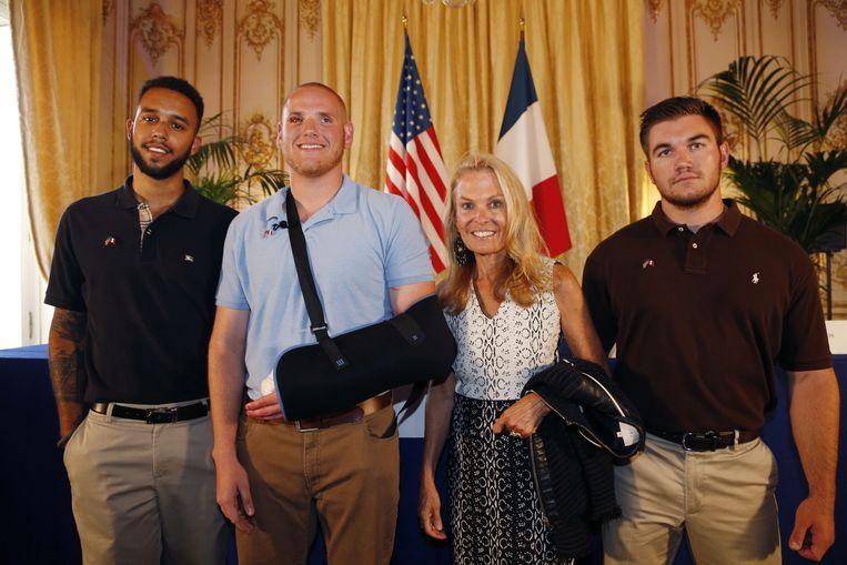 De drie Amerikanen die de schutter overmeesterden poseren met de ambassadeur van de VS in Frankrijk. Beeld AFP