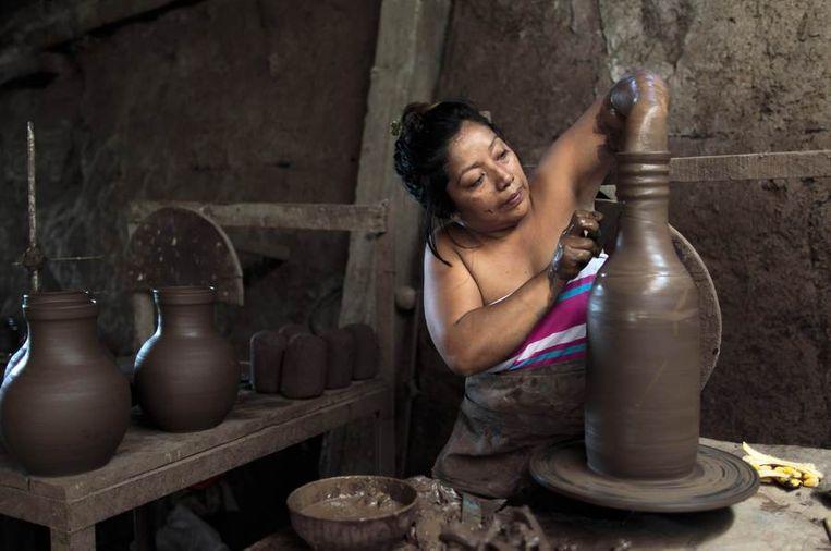 Een vrouw maakt een pot van klei, San Juan de Oriente in Nicaragua. Beeld null