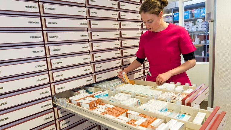 Apothekersorganisatie KNMP is terughoudender dan de Britten; 'Hoe weten apothekers wie de mensen met een sterke eigen afweer zijn?' (De apothekersassistente op de foto heeft geen relatie tot dit artikel) Beeld anp