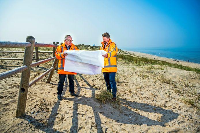 Rien van Zetten (l) en  Teun Lamers van Rijkswaterstaat bestuderen nog even de kaart waar de windmolens komen. Achter hen is een van de plekken waar een witte reus komt te staan.