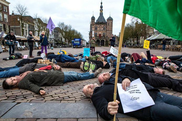 Enkele tientallen mensen houden een zogenoemde 'die-in' op de Brink in Deventer, om aandacht te vragen voor de klimaatproblematiek.