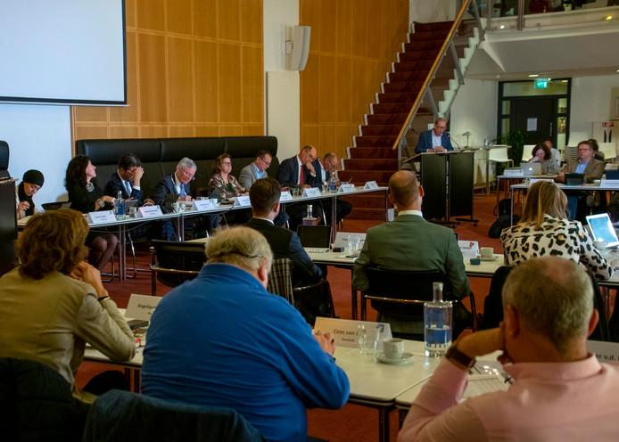 Peter van den Hoven van de LST (op de rug gezien rechts) met Burgemeester en wethouders achter de bestuurstafel en Frans van Aarle (Lokaal Tilburg) achter het spreekgestoelte.