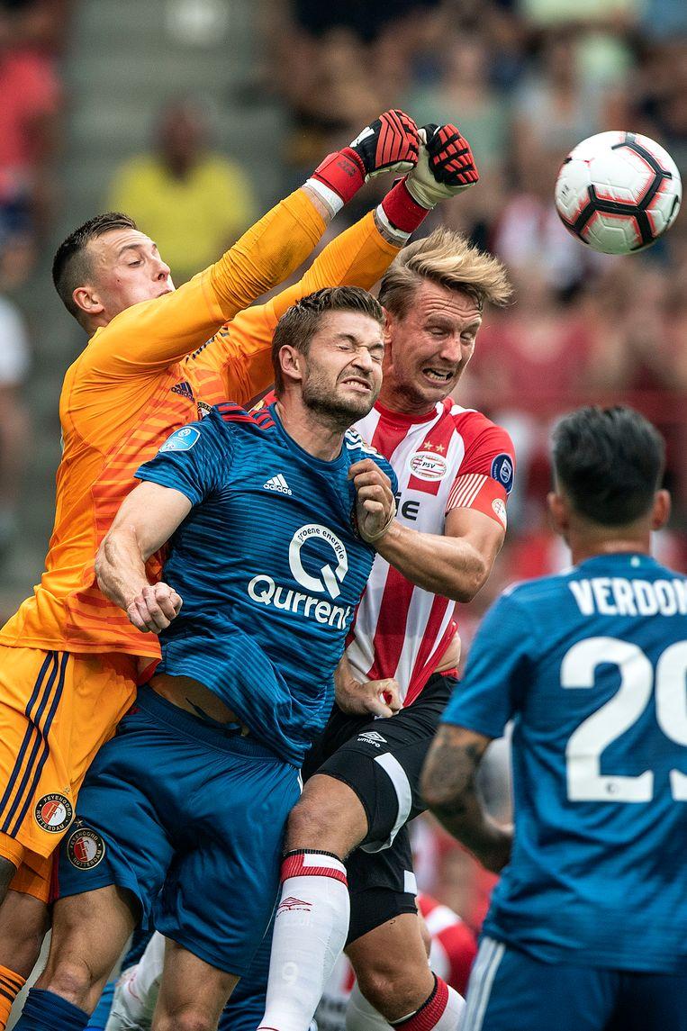 Justin Bijlow springt in de rug van Jan-Arie van der Heijden en Luuk de Jong en bokst de bal met twee vuisten weg. Beeld Guus Dubbelman / de Volkskrant